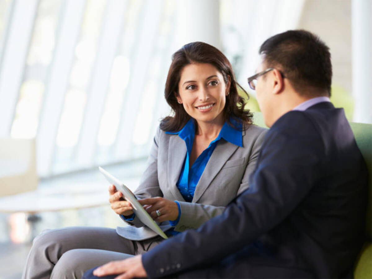 dei consultant smiling and speaking with client while pointing to tablet