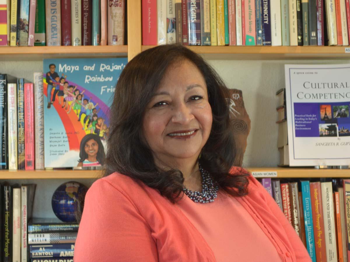 dr sangeeta gupta standing in front of bookshelf