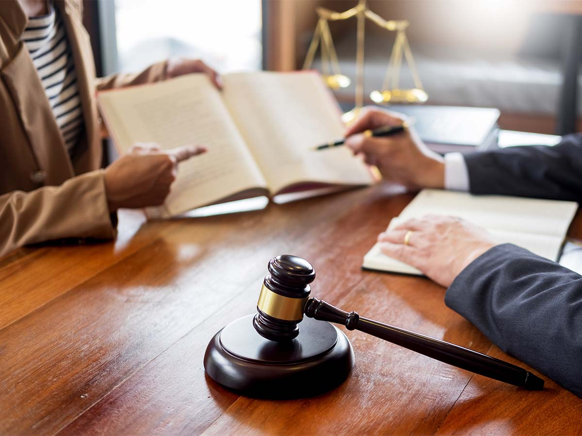 lawyer and client seated across deskdiscussing law in book